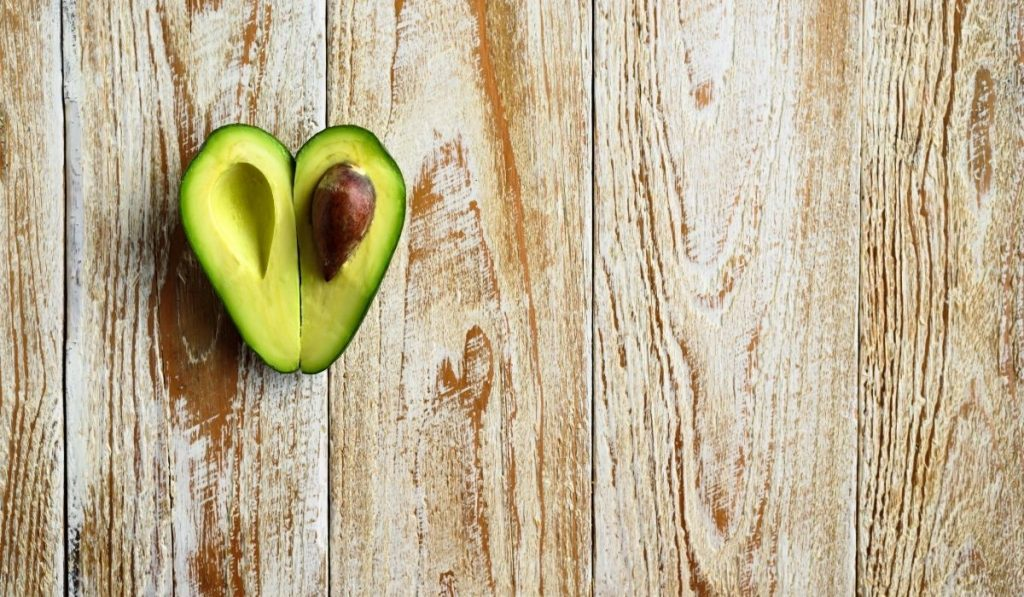 heart shaped avocado on a wooden floor