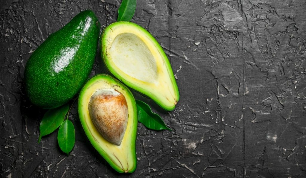 green ripe avocados with a black background