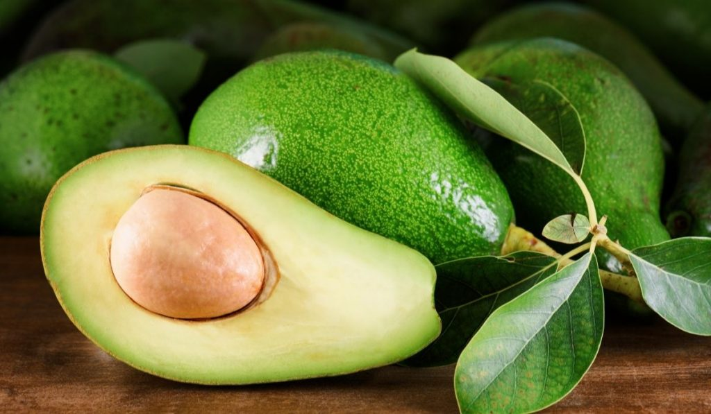 ripe green avocados with leaves on the wooden table