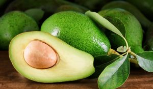 ripe-green-avocados-with-leaves-on-the-wooden-table