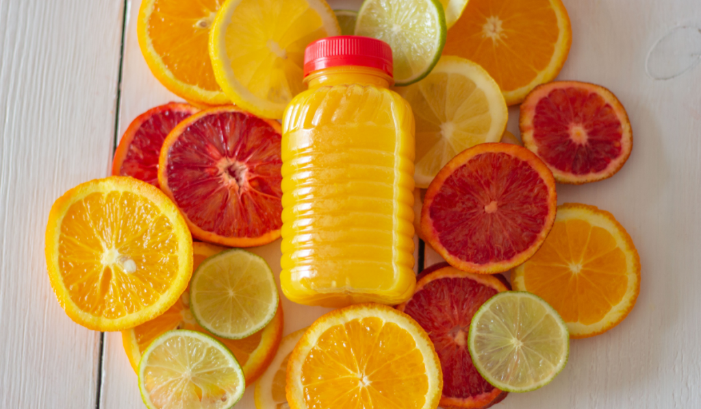 Slice of citrus fruits with its juice on the bottle