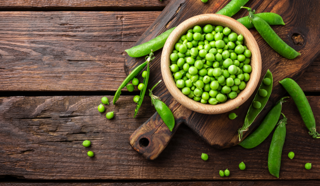 Peas on a wooden table on top of wooden chopping board.