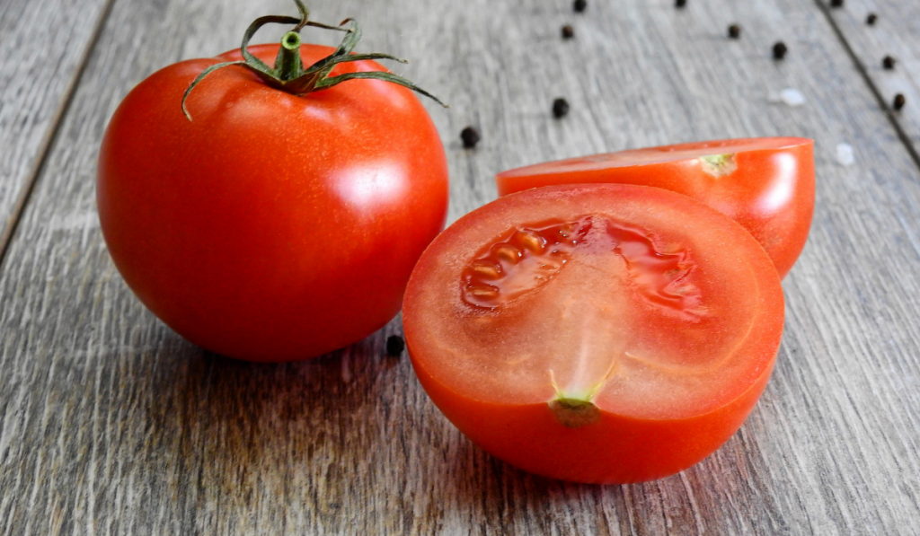 A slice tomato and tomato on wooden table.