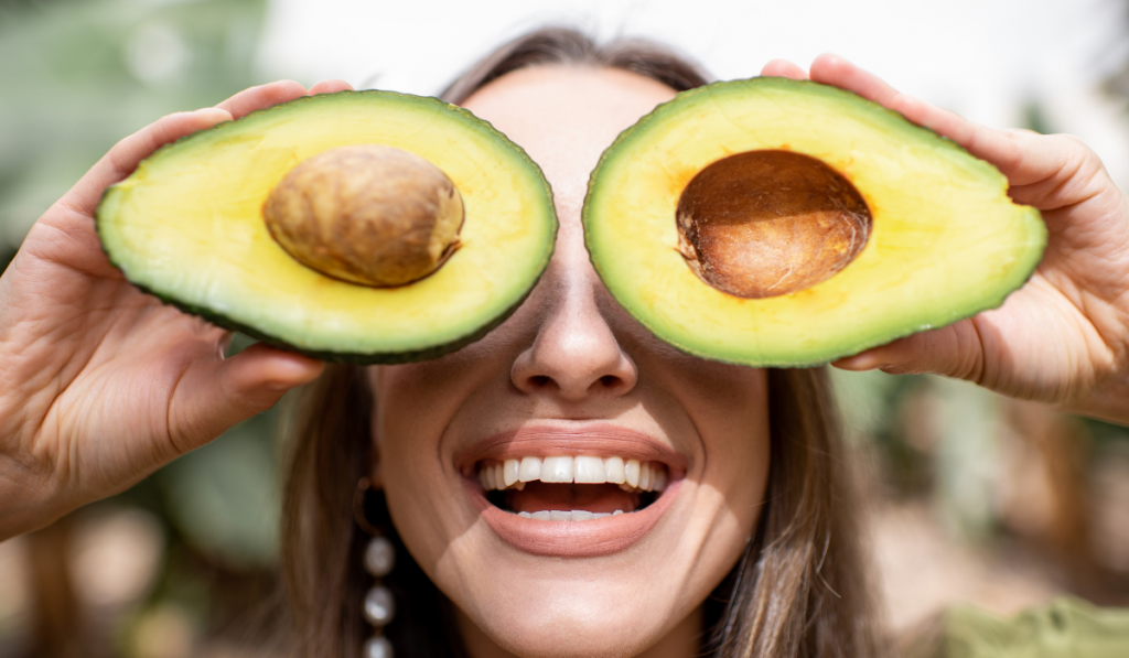 a girl smiling with sliced avocado on her eyes