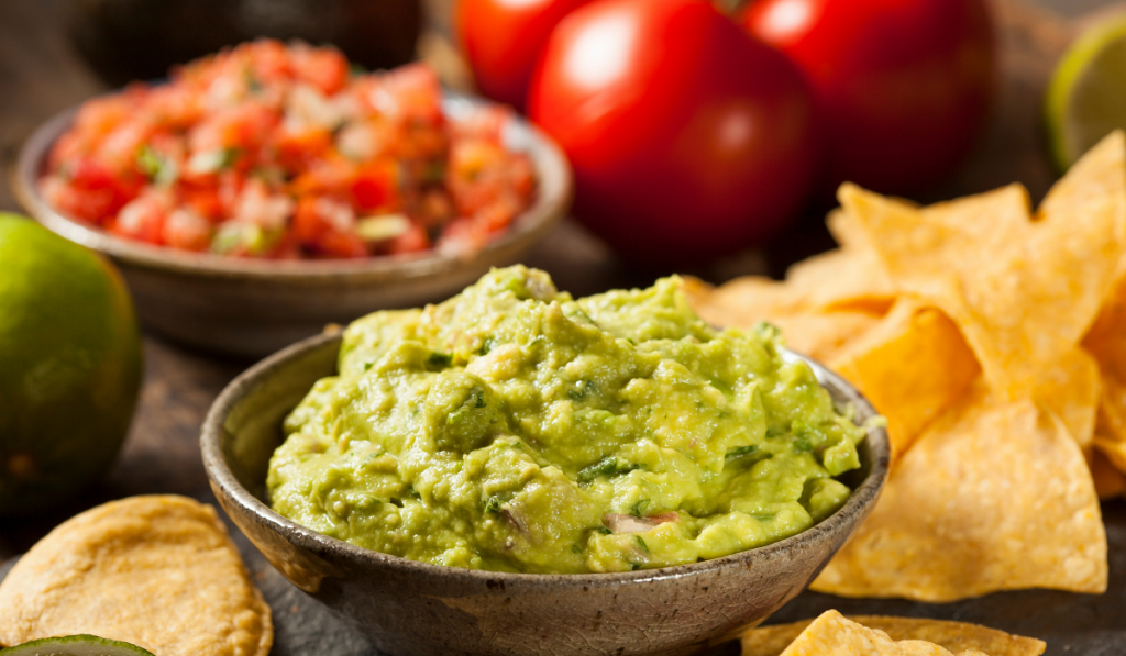 A bowl of guacamole with its ingredients in the background and chips.