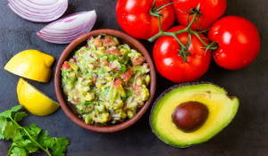 guacamole with tomatoes, onion and lemons in the background
