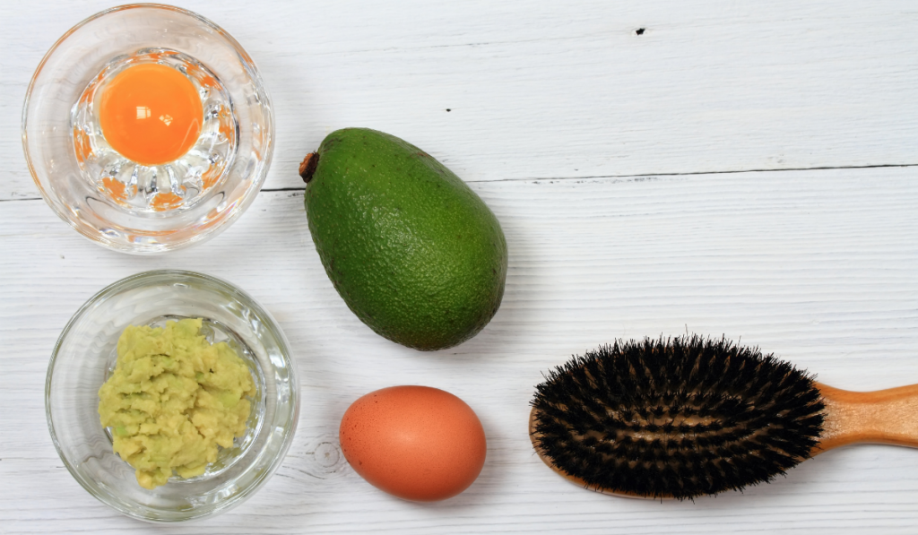 avocado an egg and a brush on a table for hair mask