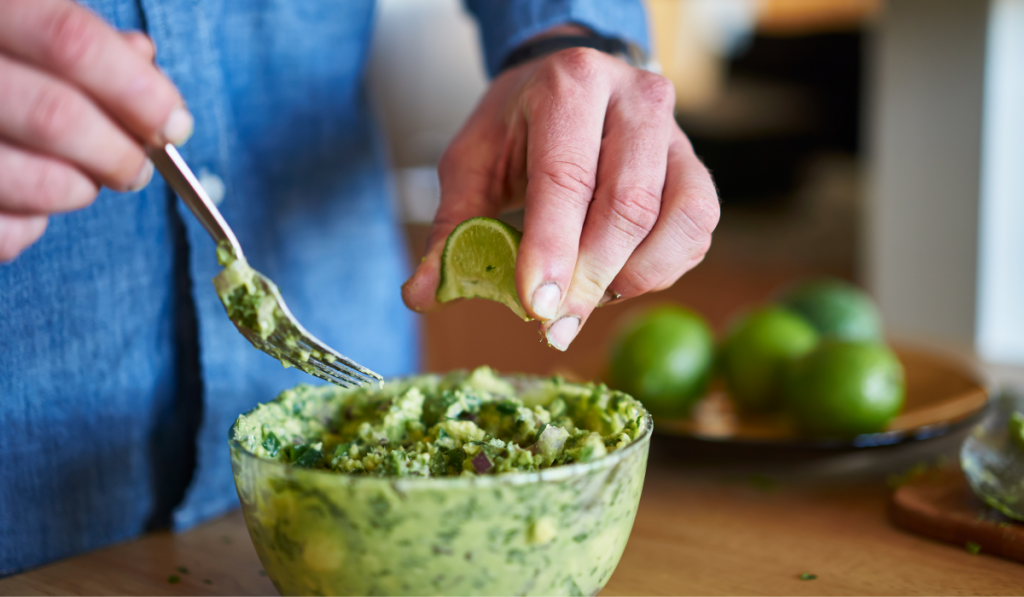 Man making guacamole and putting a lime on it