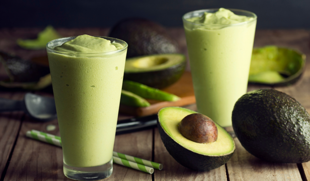 An avocado shake on a glass with slice avocado in the table.