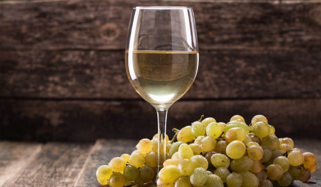 White wine on the white glass and green grapes beside the glass on wooden background.